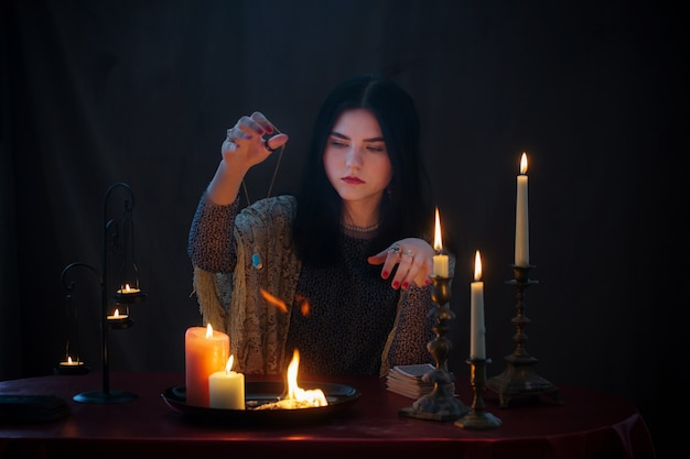 Jonge heks met vuur en brandende kaarsen op donkere ondergrond