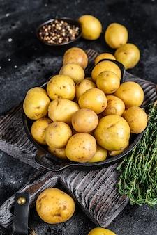 Jonge hele mini aardappelen in een pan.