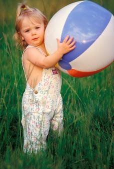 Jonge het strandbal van de meisjesholding op gebied