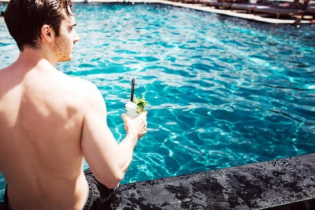 Jonge hete man rusten bij zwembad. verminder het zicht op de sterke, krachtige man die een cocktail in de hand houdt en geniet van tijd doorbrengen aan het water. zomer vakantie.