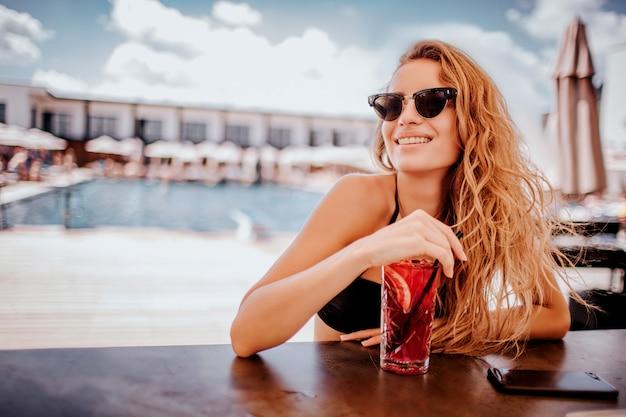 Jonge hete vrouw die bij zwembad rust