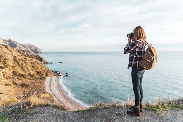 Jonge heupvrouw met een rugzak die en de kust op een mooie dag onderzoekt fotografeert. concept van exploratie en avonturen