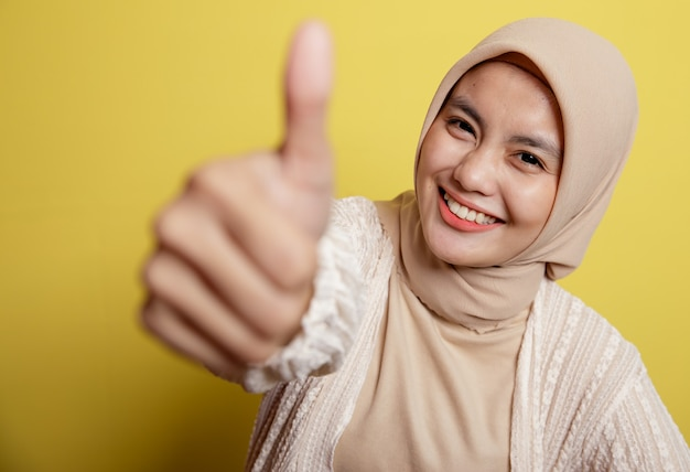 Jonge hijabvrouw die duim toont die omhoog op een gele muur wordt geïsoleerd