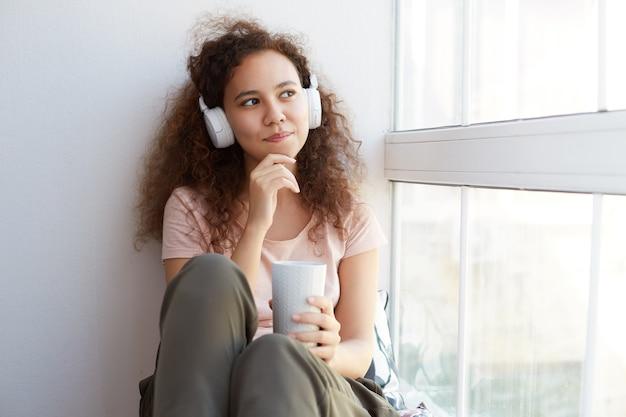 Jonge hinking krullend afro-amerikaanse dame zit bij het raam, genietend van zijn favoriete liedje en het drinken van thee, kijkt bedachtzaam weg.