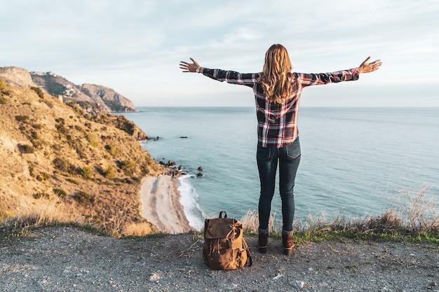 Jonge hippe vrouw met open armen en een rugzak verkent de kust op een mooie dag. concept van exploratie en avonturen