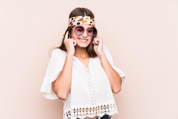 Jonge hippie kaukasische vrouw die oren behandelt met handen.