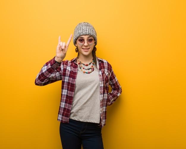 Jonge hippie natuurlijke vrouw die een rotsgebaar doet