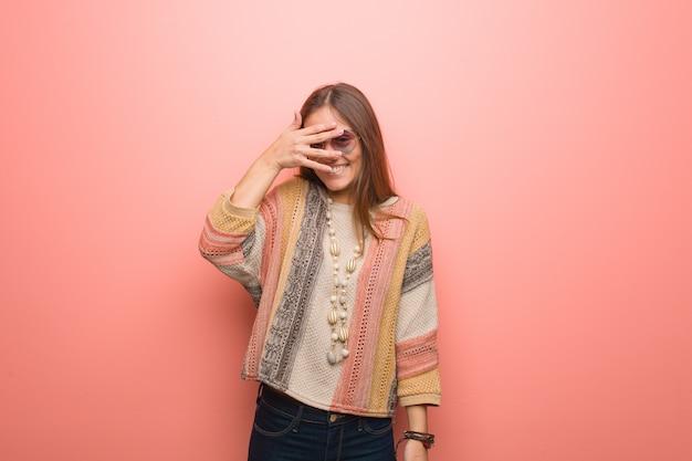 Jonge hippie vrouw op roze achtergrond pijnlijk en lachen op hetzelfde moment