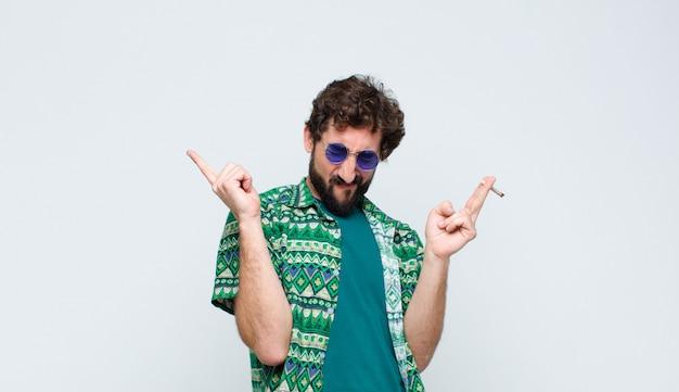 Jonge hippiemens die een verbinding rookt tegen witte muur