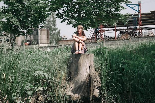 Jonge hippievrouw die dichtbij de vijver zit. het concept van eenheid met de natuur