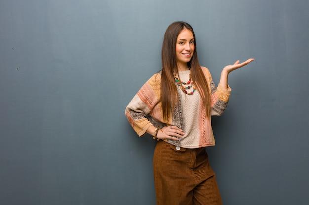 Jonge hippievrouw die iets met hand houdt