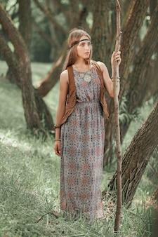 Jonge hippievrouw die met een lange stok door het bos loopt
