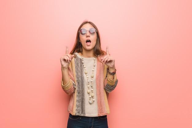 Jonge hippievrouw die omhoog wordt benadrukt om iets te tonen