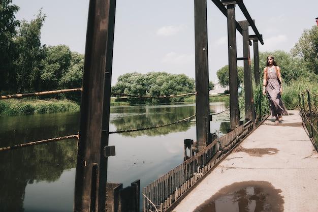 Jonge hippievrouw die op houten brug loopt