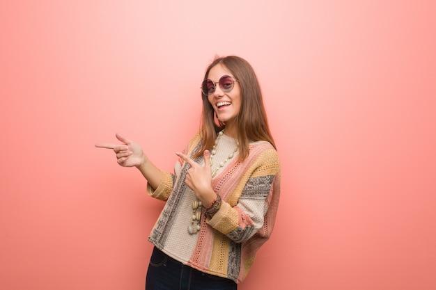 Jonge hippievrouw die op roze achtergrond aan de kant met vinger richten