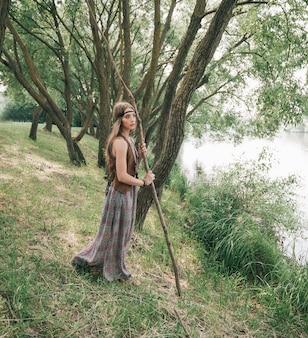 Jonge hippievrouw die zich dichtbij bosmeer bevindt