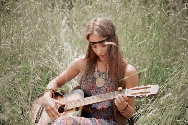 Jonge hippievrouw met gitaar zingt een lied