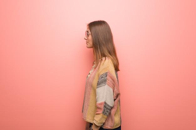 Jonge hippievrouw op roze achtergrond aan de kant die aan voorzijde kijkt
