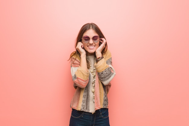 Jonge hippievrouw op roze die oren behandelen met handen