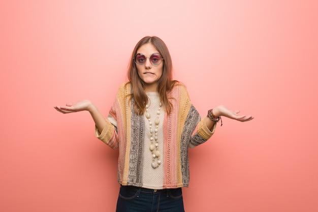 Jonge hippievrouw op roze verward en twijfelachtige achtergrond