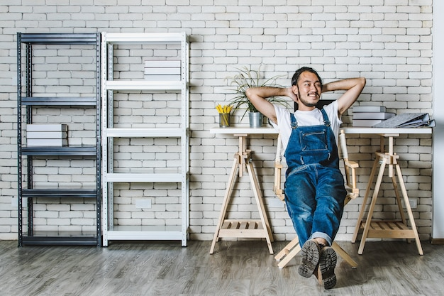 Jonge hipster baard aziatische man zit met gelukkig in zijn nieuwe moderne minimale opstartkantoor, concept voor gelukkige zakenman aan het begin.