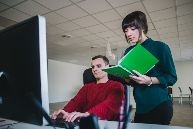 Jonge hipster collega's in het kantoor op de computer. de jeugd van nu die op kantoor werkt.
