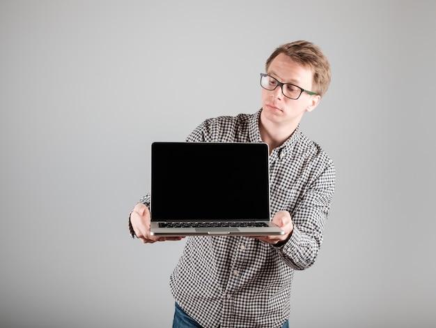 Jonge hipster die lege geïsoleerde laptop houdt