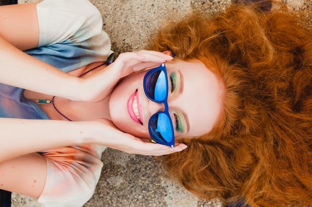 Jonge hipster gember slanke vrouw liggend bij zwembad, uitzicht van bovenaf, rood haar kleurrijk, blauwe zonnebril, sportstijl, sproeten, moedervlekken, ontspannen, gelukkig, speels, coole outfit, glimlachen, sensueel