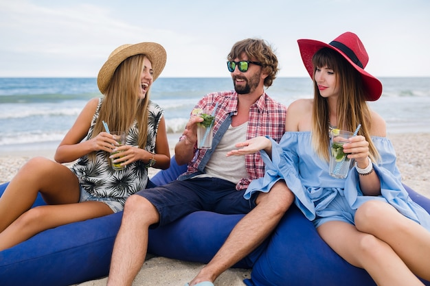 Jonge hipster gezelschap van vrienden op vakantie in strandcafé, mojito cocktail drinken, gelukkig positief, zomerstijl, glimlachend gelukkig, twee vrouwen en man die samen plezier hebben, praten, flirten, romantiek, drie