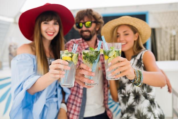 Jonge hipster gezelschap van vrienden op vakantie in zomerterras, mojito cocktails drinken, gelukkig positieve stijl, glimlachen gelukkig, twee vrouwen en man die samen plezier hebben, praten, flirten, romantiek, drie