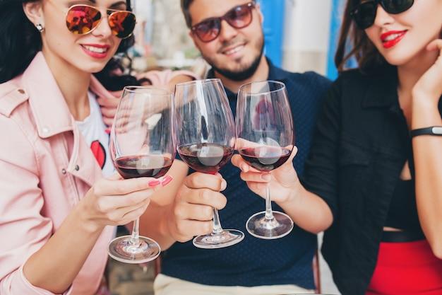Jonge hipster gezelschap van vrienden zitten in het straatcafé van de stad