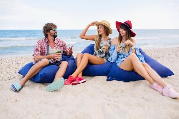 Jonge hipster glimlachend gezelschap van gelukkige vrienden op vakantie zittend in zitzakken op een strandfeest, mojito cocktail drinkend