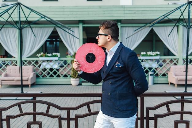 Jonge hipster in een blauw pak en witte broek drukt op zijn vinylplaat