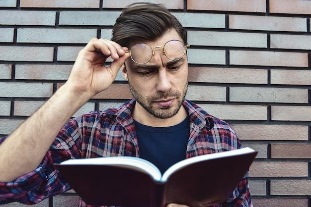 Jonge hipster kerel die een bril draagt die een boek of een notitieboek leest over bakstenen muurachtergrond.