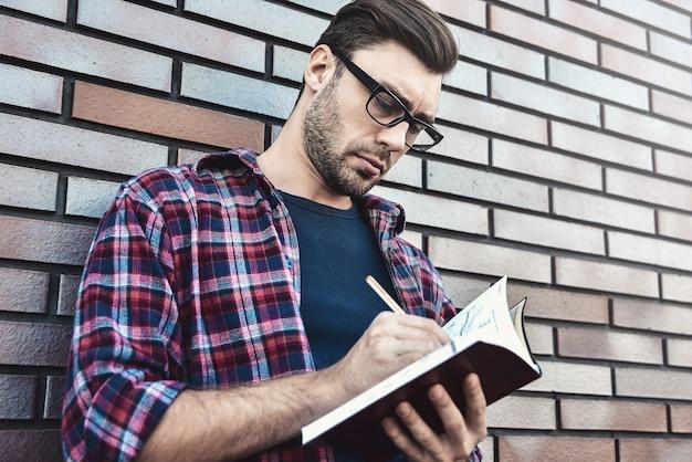 Jonge hipster kerel die een bril draagt die een boek of notitieboek leest, maakt enkele aantekeningen en ideeën op bakstenen muurachtergrond.