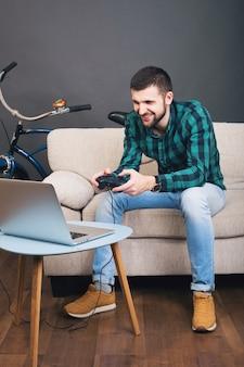 Jonge hipster knappe bebaarde man zittend op de bank thuis, videogame spelen op notebook