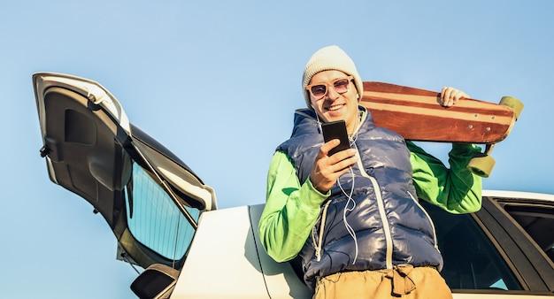 Jonge hipster knappe man met mobiele slimme telefoon luisteren muziek tijdens autorit