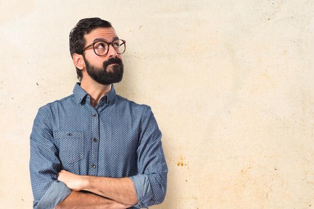 Jonge hipster man denken over witte achtergrond