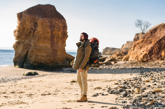 Jonge hipster man die alleen reist met rugzak in de herfstzeekust met een warme jas en muts