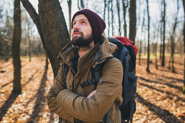 Jonge hipster man die met rugzak reist in het herfstbos met een warme jas en muts