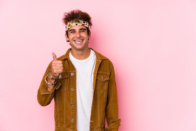 Jonge hipster man geïsoleerd jonge man gaat naar een festival glimlachend en duim omhoog