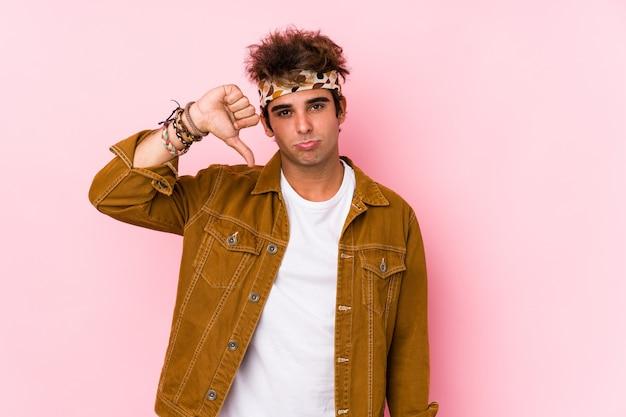 Jonge hipster man geïsoleerd jonge man gaat naar een festival met een afkeer gebaar, duimen naar beneden. meningsverschil concept.