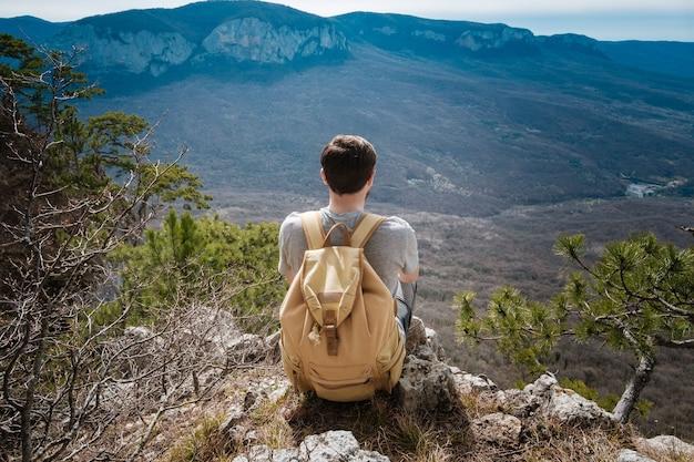 Jonge hipster man in de bergen van de lente. hipster met een rugzak achter zijn rug gaat op reis
