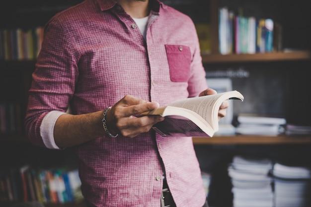 Jonge hipster man lezen boek in de bibliotheek.