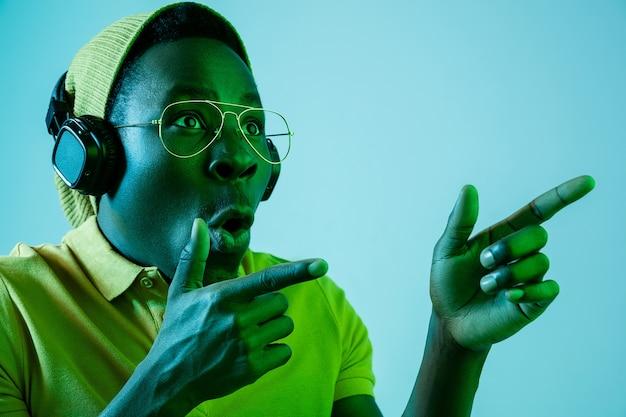 Jonge hipster man luisteren muziek met koptelefoon op blauwe studio met neonlichten. emotionele uitdrukking
