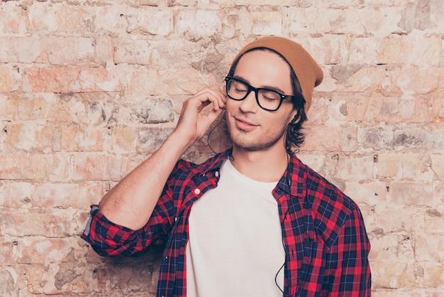 Jonge hipster man luisteren naar muziek op de koptelefoon