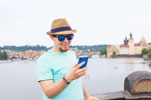Jonge hipster man met behulp van mobiele slimme telefoon buiten