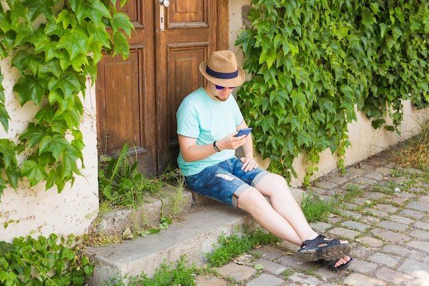 Jonge hipster man met behulp van mobiele slimme telefoon buitenshuis