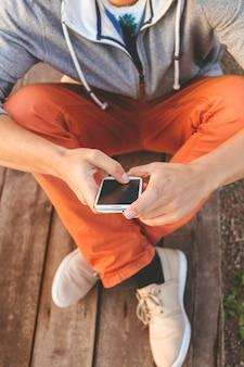 Jonge hipster man met behulp van slimme telefoon zittend op houten planken