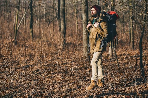 Jonge hipster man reizen met rugzak in herfst bos dragen warme jas en hoed, actieve toerist, natuur in koude seizoen verkennen